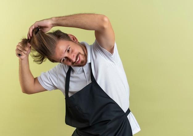 Zadowolony młody przystojny fryzjer ubrany w mundur czeszący włosy, patrząc z boku odizolowany na oliwkowej ścianie