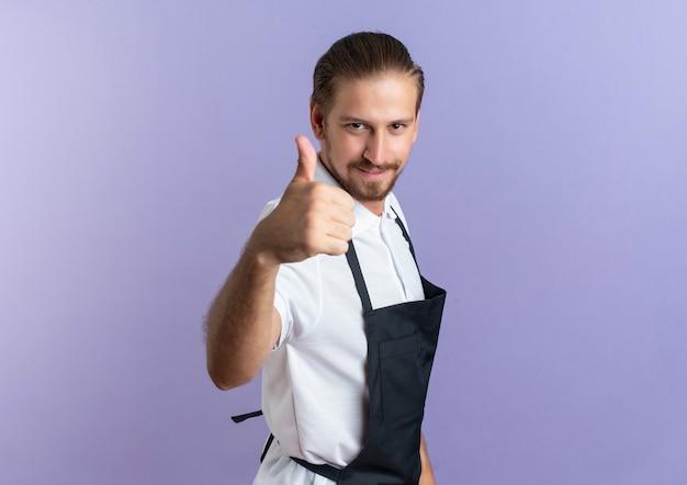 Zadowolony młody przystojny fryzjer w mundurze stojącym w widoku profilu pokazujący kciuk do góry na białym tle na fioletowej ścianie