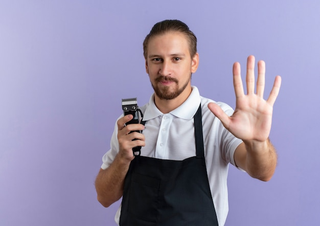 Zadowolony młody przystojny fryzjer w mundurze, trzymając maszynkę do strzyżenia włosów i wyciągając rękę do przodu na białym tle na fioletowej ścianie