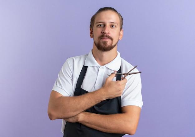 Zadowolony młody przystojny fryzjer w mundurze trzymając nożyczki na białym tle na fioletowej ścianie