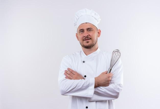 Zadowolony młody przystojny kucharz w mundurze szefa kuchni stojącej z zamkniętą postawą i trzymając trzepaczkę na białym tle