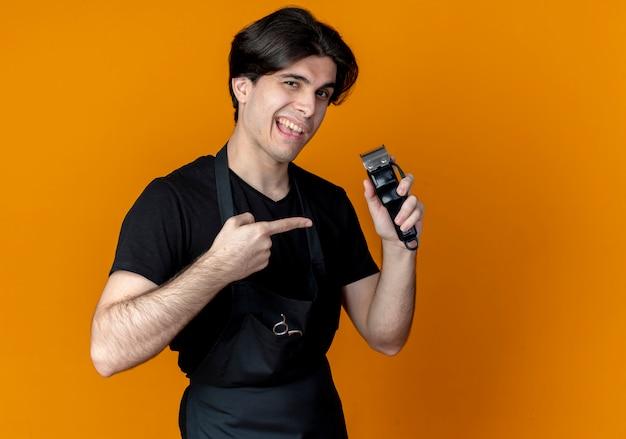 Zadowolony młody przystojny mężczyzna fryzjer w mundurze gospodarstwa i wskazuje na maszynkę do strzyżenia włosów na pomarańczowo