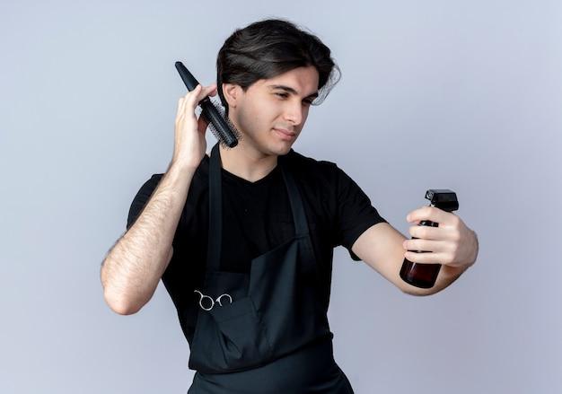 Zadowolony młody przystojny mężczyzna fryzjer w mundurze, trzymając grzebień wokół głowy i patrząc na butelkę z rozpylaczem w ręku na białej ścianie