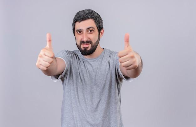 Zadowolony młody przystojny mężczyzna pokazując kciuki do góry z przodu na białym tle na białej ścianie