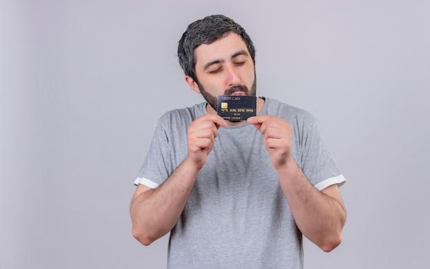 Zadowolony młody przystojny mężczyzna trzyma i całuje kartę kredytową z zamkniętymi oczami na białym tle na białej ścianie