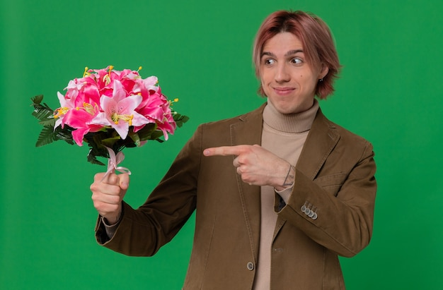 Zadowolony młody przystojny mężczyzna trzymający i wskazujący na bukiet kwiatów
