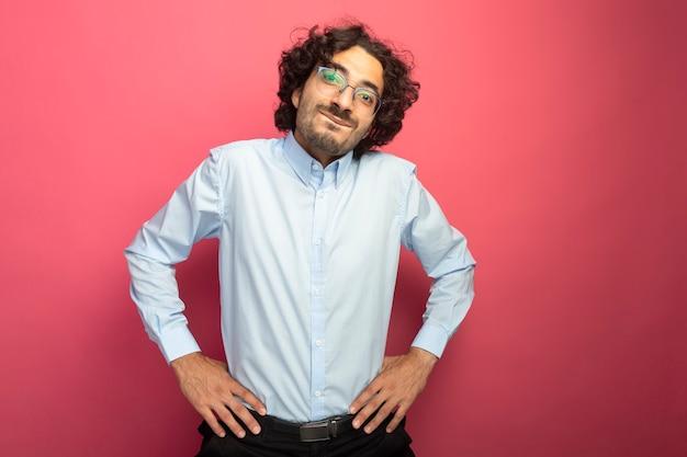 Zadowolony młody przystojny mężczyzna w okularach, patrząc z przodu, trzymając ręce w talii na białym tle na różowej ścianie