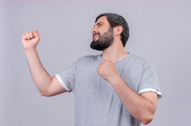 Zadowolony młody przystojny mężczyzna zaciskając pięści z zamkniętymi oczami na białym tle na białej ścianie
