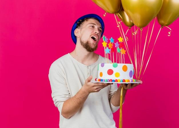 Zadowolony młody przystojny słowiański imprezowicz w kapeluszu imprezowym, trzymający balony i tort urodzinowy z gwiazdami, patrząc prosto na różowej ścianie z miejscem na kopię