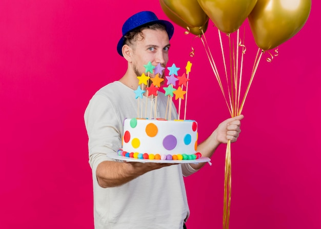 Zadowolony młody przystojny słowiański imprezowicz w kapeluszu imprezowym, trzymający balony i wyciągający tort urodzinowy z gwiazdami do przodu, patrząc z przodu odizolowany na różowej ścianie z miejscem na kopię