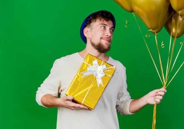 Zadowolony młody przystojny słowiański partyjny facet w kapeluszu z balonów i pudełko, patrząc na balony na białym tle na zielonym tle