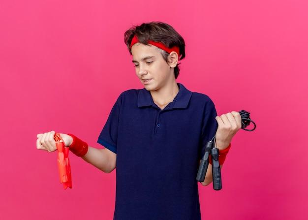 Zadowolony młody przystojny sportowy chłopiec z opaską i opaskami na nadgarstki z aparatem ortodontycznym trzymający i patrząc na skakanki odizolowane na szkarłatnej ścianie
