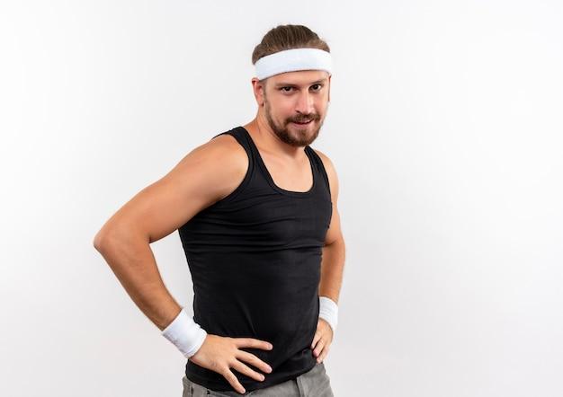 Zadowolony młody przystojny sportowy mężczyzna ubrany w opaskę i opaski na rękę kładąc ręce na talii na białym tle na białej przestrzeni