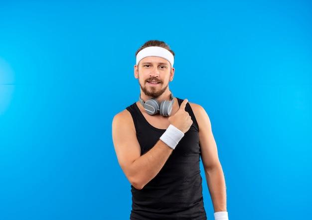 Zadowolony młody przystojny sportowy mężczyzna z opaską i opaskami na nadgarstki i słuchawkami na szyi, wskazując na bok na białym tle na niebieskiej przestrzeni