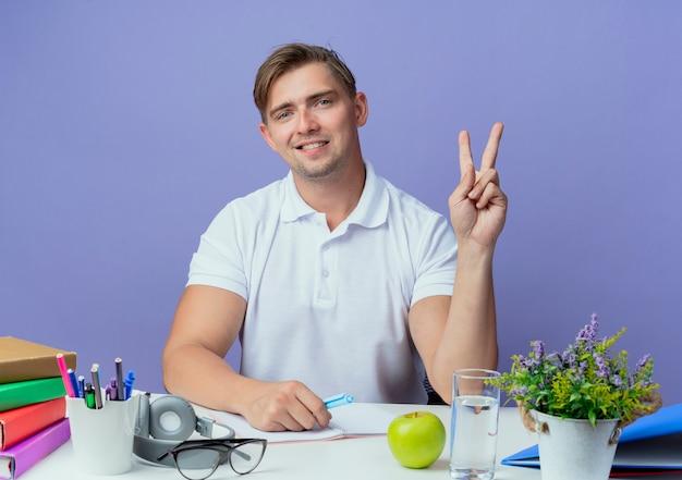 Zadowolony młody przystojny student płci męskiej siedzi przy biurku z narzędziami szkolnymi pokazując gest pokoju na niebieskim tle