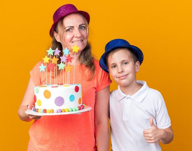 Zadowolony młody słowiański chłopiec w niebieskiej imprezowej czapce kciukiem w górę stojący z matką w fioletowym imprezowym kapeluszu i trzymający tort urodzinowy odizolowany na pomarańczowej ścianie z kopią miejsca