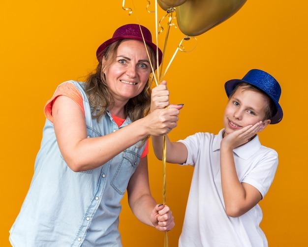 Zadowolony młody słowiański chłopiec w niebieskiej imprezowej czapce kładący rękę na twarzy i trzymający balony z helem z matką w fioletowym imprezowym kapeluszu odizolowanym na pomarańczowej ścianie z kopią miejsca