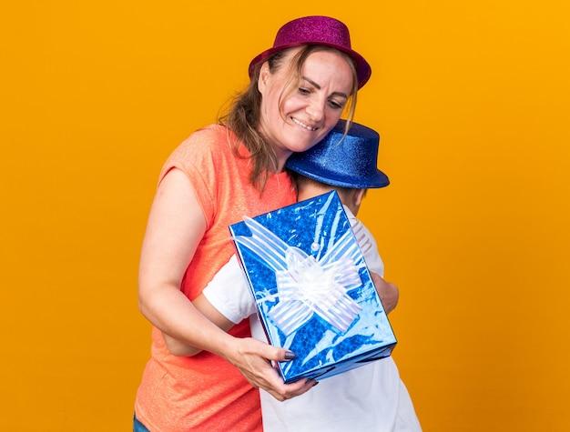 Zadowolony młody słowiański chłopiec w niebieskiej imprezowej czapce przytulający matkę w fioletowym kapeluszu imprezowym i trzymający pudełko na białym tle na pomarańczowej ścianie z kopią miejsca