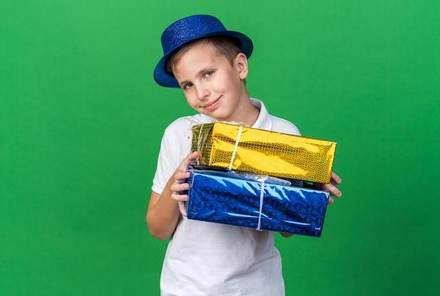 Zadowolony młody słowiański chłopiec w niebieskiej imprezowej czapce trzymający pudełka na prezenty na zielonej ścianie z miejscem na kopię