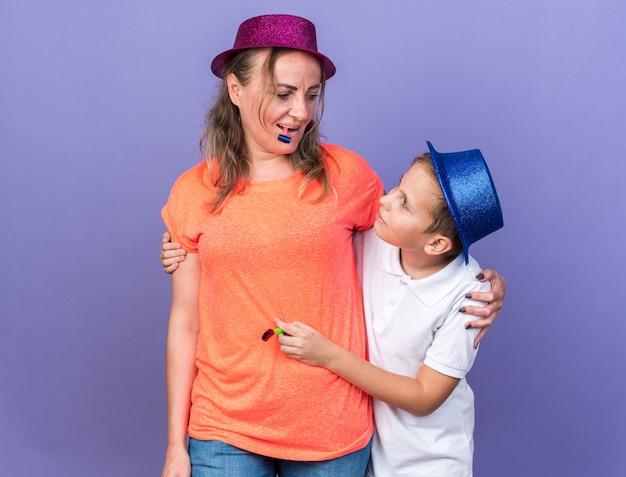 Zadowolony młody słowiański chłopiec z niebieskim czapką imprezową, trzymając gwizdek imprezowy i stojąc z matką w fioletowym kapeluszu imprezowym i dmuchającym gwizdkiem na imprezie na fioletowej ścianie z miejscem na kopię