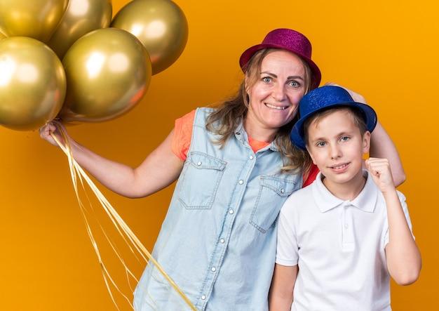 Zadowolony młody słowiański chłopiec z niebieskim kapeluszem imprezowym trzymającym pięść w górze i stojącym z matką w fioletowym kapeluszu imprezowym trzymającym balony z helem odizolowane na pomarańczowej ścianie z miejscem na kopię