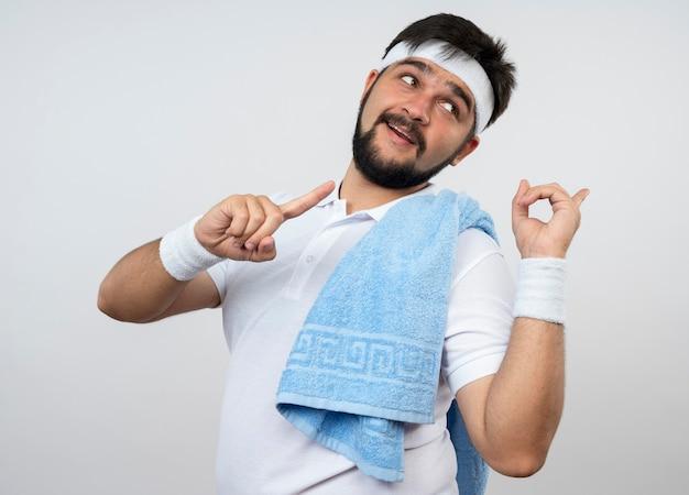 Zadowolony młody sportowiec patrząc z boku, nosząc opaskę na głowę i opaskę z ręcznikiem na ramionach z boku na białej ścianie