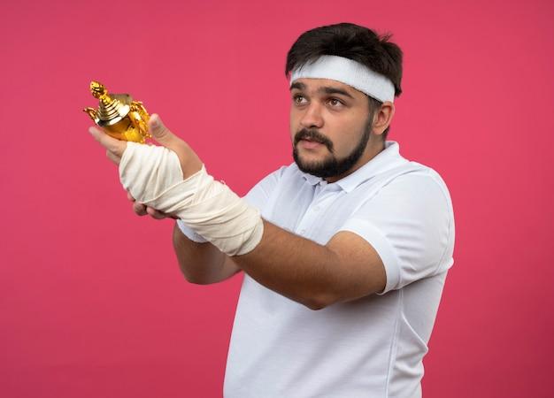 Zadowolony młody sportowiec, patrząc z boku, noszący opaskę na głowę i opaskę z nadgarstkiem owiniętym bandażem, trzymający z boku puchar zwycięzcy