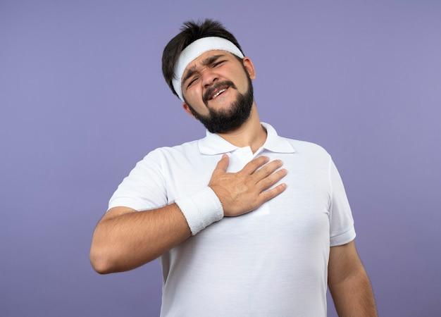 Zadowolony młody sportowiec w opasce i opasce kładzie rękę na piersi