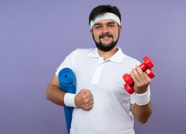 Zadowolony młody sportowiec z opaską na głowę i nadgarstkiem, trzymając hantle z matą do jogi