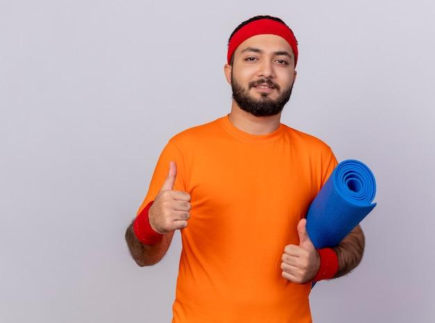 Zadowolony młody sportowiec z opaską na głowę i nadgarstkiem, trzymając matę do jogi