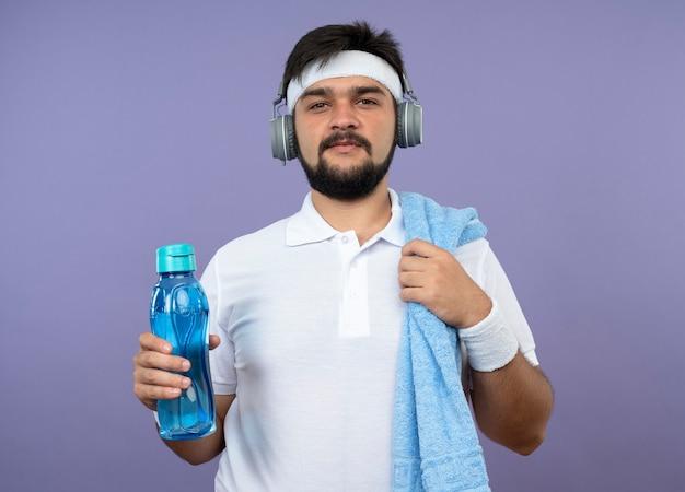 Zadowolony młody sportowiec z opaską na głowę i nadgarstkiem ze słuchawkami, trzymając butelkę wody z ręcznikiem na ramieniu