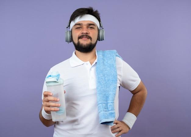 Zadowolony młody sportowiec z opaską na głowę i nadgarstkiem ze słuchawkami, trzymając butelkę z wodą z ręcznikiem na ramieniu, kładąc rękę na biodrze