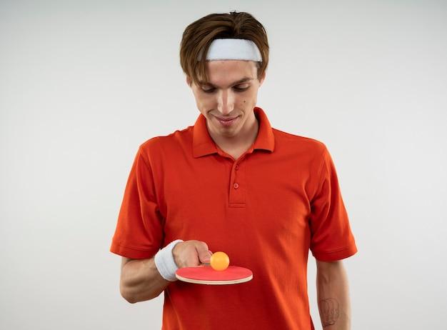 Zadowolony młody sportowy facet ubrany w opaskę z opaską, trzymając i patrząc na rakietę do ping-ponga z piłką na białym tle na białej ścianie