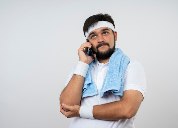 Zadowolony młody sportowy mężczyzna patrząc w górę z opaską na głowę i opaską na rękę z ręcznikiem na ramieniu mówi przez telefon na białej ścianie z miejscem na kopię