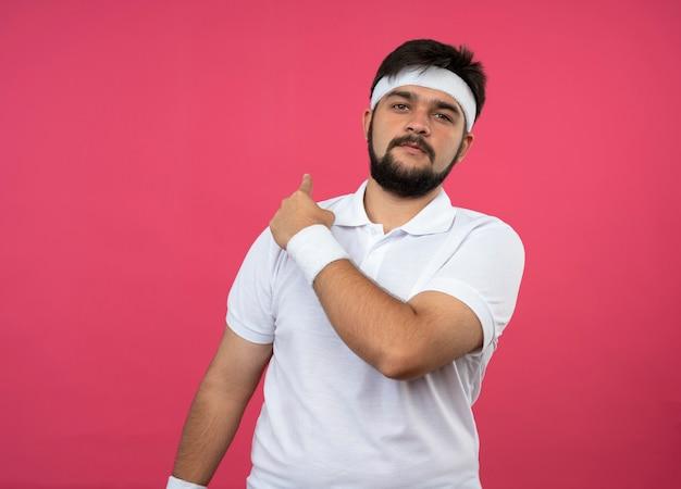 Zadowolony młody sportowy mężczyzna z opaską na głowę i opaską wskazuje na tył odizolowane na różowej ścianie z miejscem na kopię