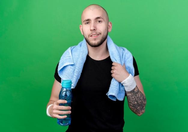 Zadowolony młody sportowy mężczyzna z opaską na nadgarstku, trzymając butelkę wody z ręcznikiem na ramieniu na białym tle na zielonej ścianie