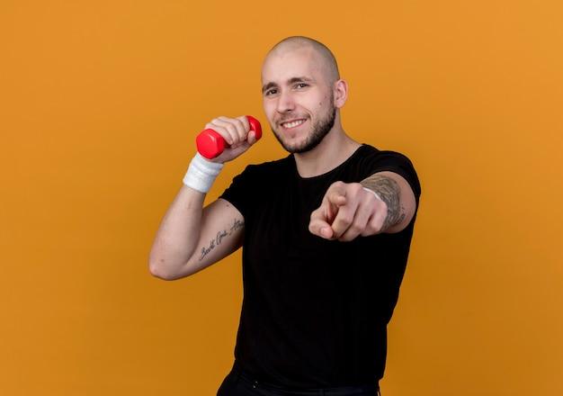 Zadowolony młody sportowy mężczyzna z opaską na rękę, trzymając hantle na ramieniu i pokazując gest na pomarańczowo