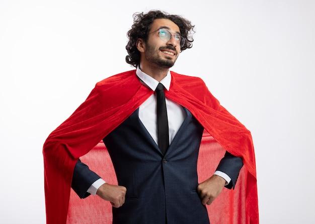 Zadowolony młody superbohater w okularach optycznych w garniturze z czerwonym płaszczem kładzie ręce na talii i patrzy w górę na białej ścianie