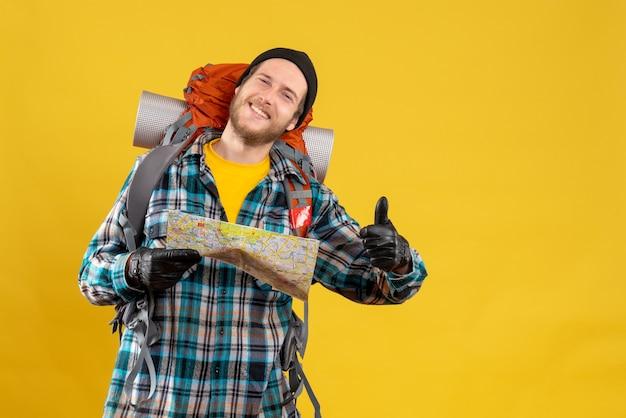 Zadowolony młody turysta ze skórzanymi rękawiczkami i plecakiem trzymającym mapę z kciukiem do góry
