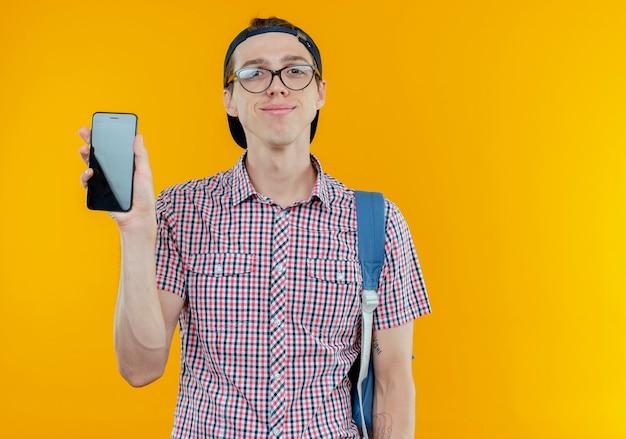 Zadowolony młody uczeń chłopiec nosi torbę z powrotem i okulary i czapkę trzymając telefon