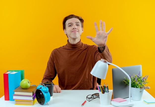 Zadowolony młody uczeń chłopiec siedzi przy biurku z narzędzi szkolnych pokazując pięć na białym tle na żółtej ścianie