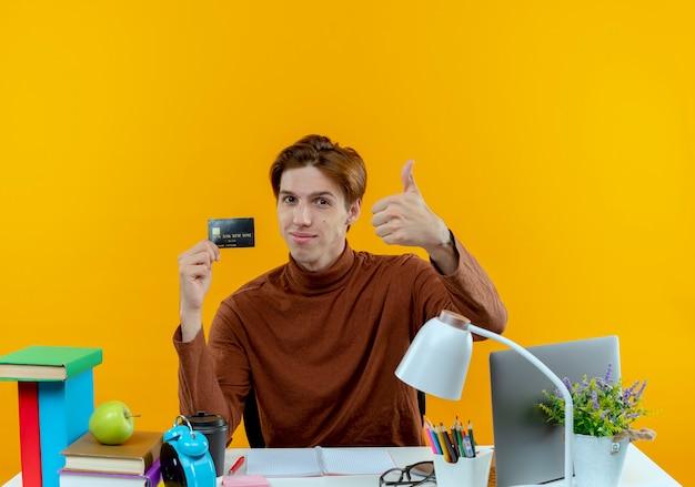Zadowolony młody uczeń chłopiec siedzi przy biurku z narzędzi szkolnych, trzymając kartę kredytową kciuk w górę
