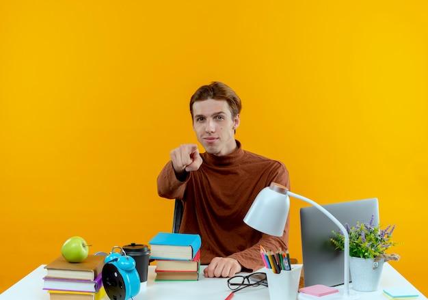 Zadowolony młody uczeń chłopiec siedzi przy biurku z narzędziami szkolnymi, pokazując gest na białym tle na żółtej ścianie