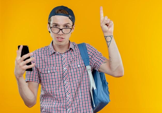 Zadowolony młody uczeń chłopiec ubrany w torbę i okulary i czapkę trzymając telefon i wskazuje na górę