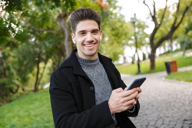 Zadowolony młody wesoły człowiek w odzieży casual spaceru na świeżym powietrzu w zielonym parku przy użyciu telefonu komórkowego słuchania muzyki przez słuchawki.
