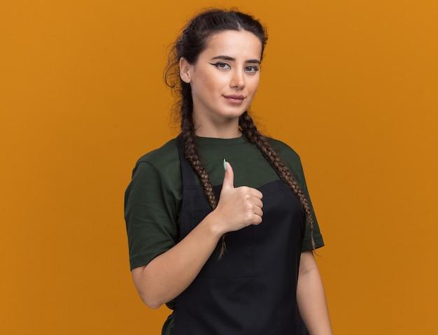 Zadowolony młody żeński fryzjer w mundurze pokazując kciuk do góry na białym tle na pomarańczowej ścianie