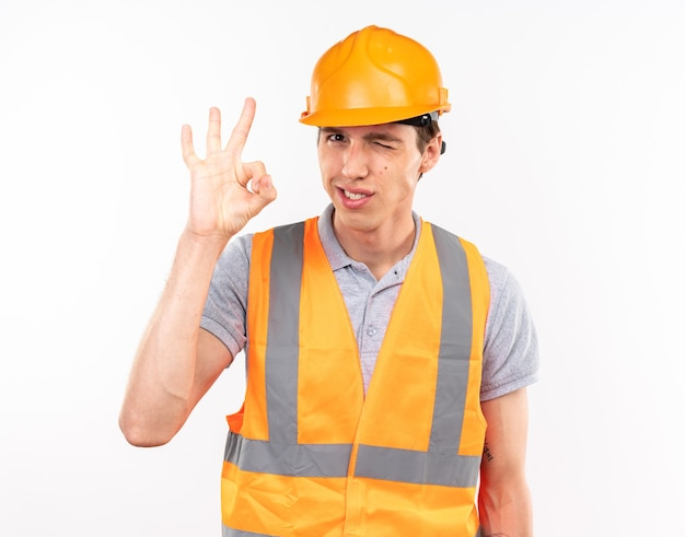Zadowolony, mrugający, młody budowniczy mężczyzna w mundurze pokazujący dobry gest na białej ścianie
