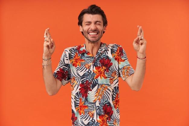 Zadowolony, natchniony młody mężczyzna z zarostem i zamkniętymi oczami w hawajskiej koszuli trzyma kciuki i wypowiada życzenie