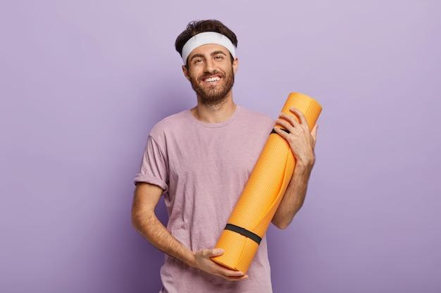 Zadowolony nieogolony mężczyzna trzyma zwiniętą matę fitness, zadowolony po zajęciach jogi