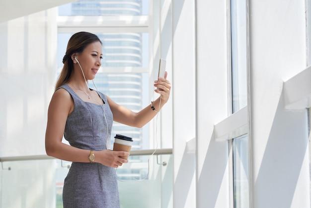Zadowolony nowoczesna młoda azjatycka bizneswoman w słuchawkach pijąca kawę i rozmawiająca z klientem przez czat wideo w biurze